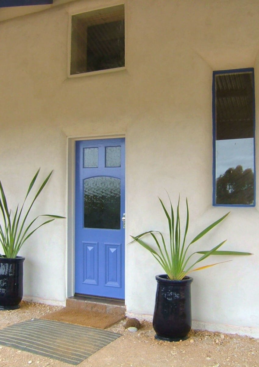 Blue front door of a beautiful straw bale house