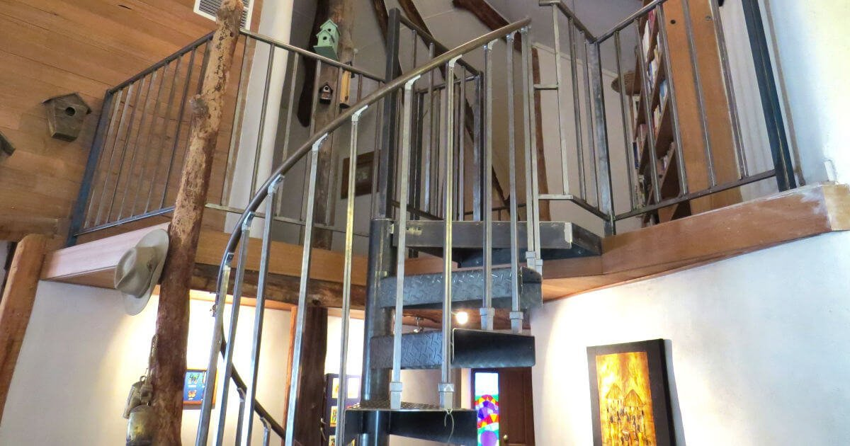 Spiral staircase leading up to a straw bale mezzanine